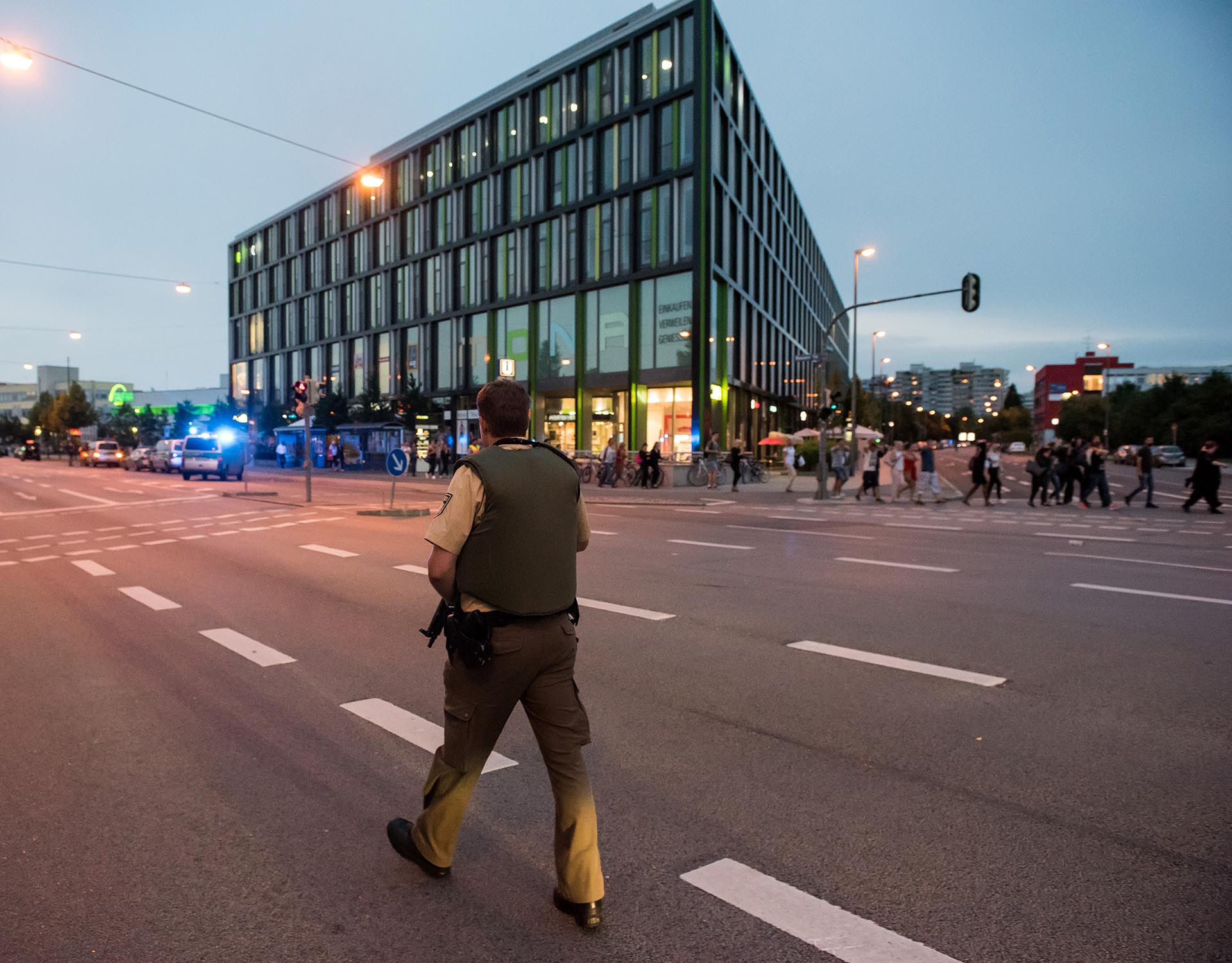 A policeman patrols as people are beeing evacuated (R) from a shopping mall in Munich on July 22, 2016 following a shooting earlier. At least one person has been killed and 10 wounded in a shooting at a shopping centre in Munich on Friday, German police said. / AFP PHOTO / STRINGER